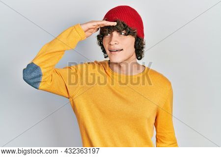Handsome young man wearing wool hat very happy and smiling looking far away with hand over head. searching concept.