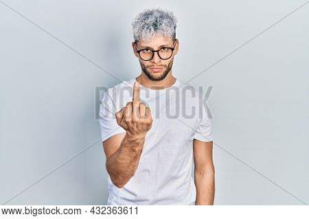 Young hispanic man with modern dyed hair wearing white t shirt and glasses showing middle finger, impolite and rude fuck off expression