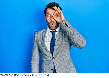 Handsome man with beard wearing business suit and tie doing ok gesture shocked with surprised face, eye looking through fingers. unbelieving expression.