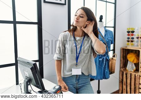 Young brunette woman working as manager at retail boutique smiling with hand over ear listening an hearing to rumor or gossip. deafness concept.