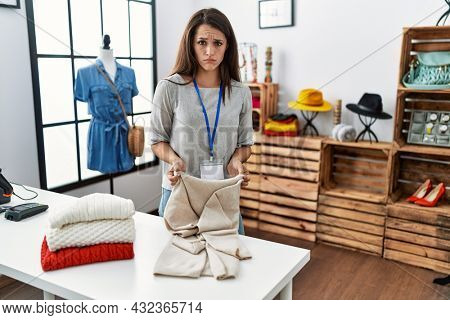 Young brunette woman working at retail boutique skeptic and nervous, frowning upset because of problem. negative person.