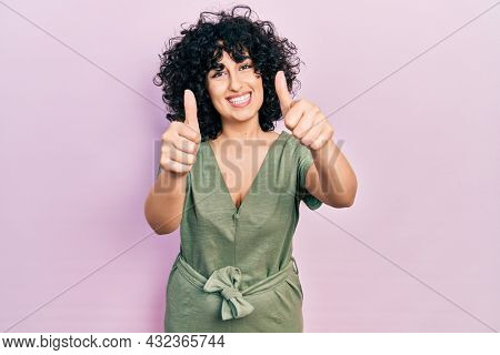 Young middle east woman wearing casual clothes approving doing positive gesture with hand, thumbs up smiling and happy for success. winner gesture.