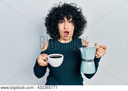 Young middle east woman holding italian coffee maker afraid and shocked with surprise and amazed expression, fear and excited face.