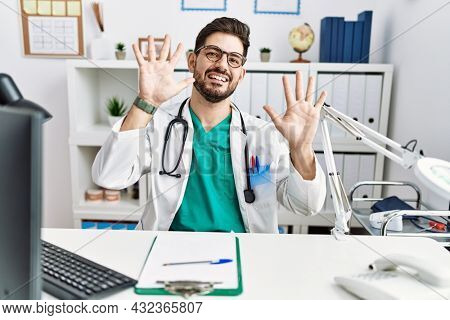 Young man with beard wearing doctor uniform and stethoscope at the clinic showing and pointing up with fingers number ten while smiling confident and happy.