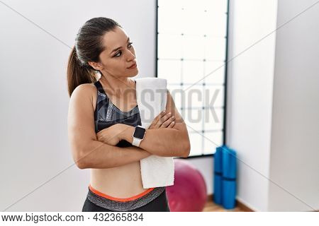 Young brunette woman wearing sportswear and towel at the gym looking to the side with arms crossed convinced and confident