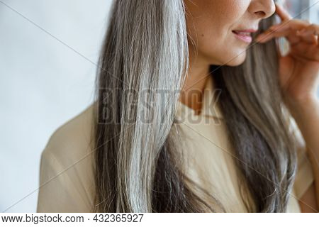 Middle Aged Woman With Beautiful Grey Hair Poses On Light Grey Background
