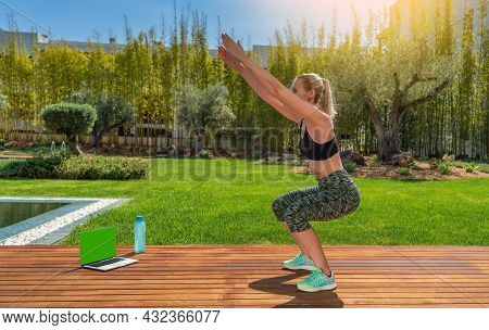 Athletic European Girl Doing Squats Outside In The Park With An Online Fitness Instructor. Sunny Day