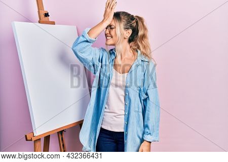 Beautiful young blonde woman standing by white painter easel stand surprised with hand on head for mistake, remember error. forgot, bad memory concept.