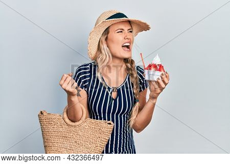 Beautiful young blonde woman wearing summer style eating ice cream angry and mad screaming frustrated and furious, shouting with anger. rage and aggressive concept.