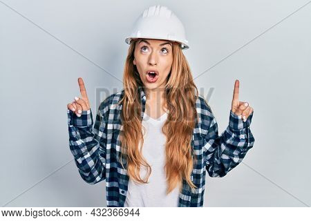 Young caucasian woman wearing architect hardhat amazed and surprised looking up and pointing with fingers and raised arms.