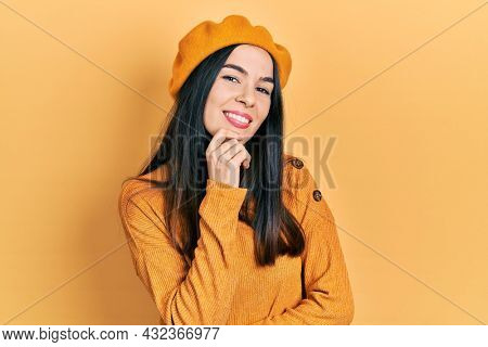 Young brunette woman wearing french look with beret smiling looking confident at the camera with crossed arms and hand on chin. thinking positive.