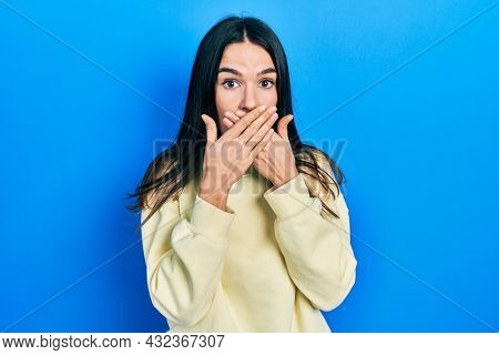 Young brunette woman wearing casual sweatshirt shocked covering mouth with hands for mistake. secret concept.