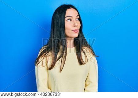 Young brunette woman wearing casual sweatshirt smiling looking to the side and staring away thinking.