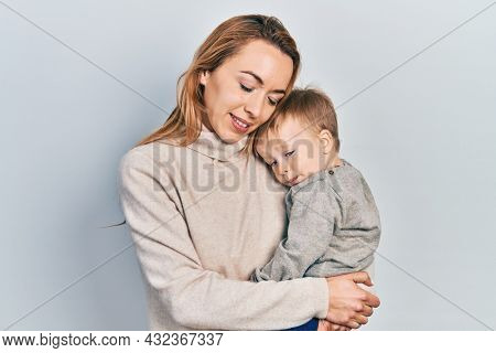 Young caucasian woman holding and hugging her son with love. Family of two bonding together. Mother holding infant toddler
