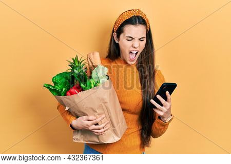 Young brunette teenager holding bag of groceries using smartphone angry and mad screaming frustrated and furious, shouting with anger. rage and aggressive concept.