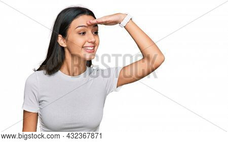 Young hispanic girl wearing casual white t shirt very happy and smiling looking far away with hand over head. searching concept.