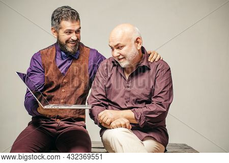 Adult Learning And Education. Happy Young Man With Senior Dad Have Fun Watching Funny Video On Lapto