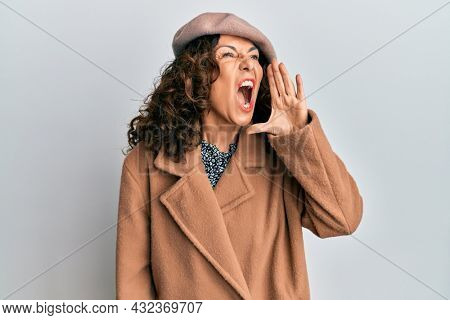 Middle age hispanic woman wearing french look with beret shouting and screaming loud to side with hand on mouth. communication concept.