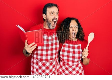 Middle age couple of hispanic woman and man wearing professional apron reading cooking recipe book angry and mad screaming frustrated and furious, shouting with anger. rage and aggressive concept.
