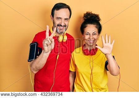 Middle age couple of hispanic woman and man wearing sportswear and arm band showing and pointing up with fingers number seven while smiling confident and happy.