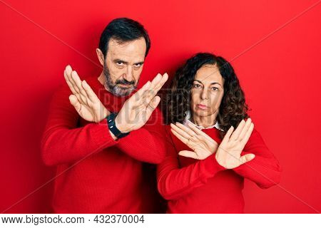 Middle age couple of hispanic woman and man hugging and standing together rejection expression crossing arms and palms doing negative sign, angry face