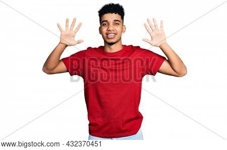Young african american man wearing casual red t shirt showing and pointing up with fingers number ten while smiling confident and happy.