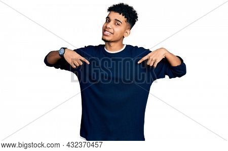Young african american man wearing casual clothes looking confident with smile on face, pointing oneself with fingers proud and happy.