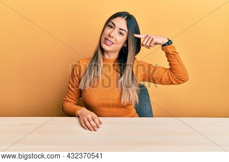 Young hispanic woman wearing casual clothes sitting on the table smiling pointing to head with one finger, great idea or thought, good memory
