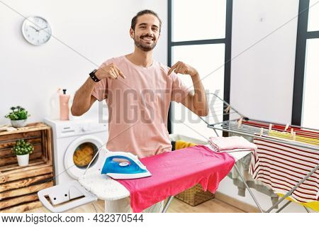 Young hispanic man ironing clothes at home looking confident with smile on face, pointing oneself with fingers proud and happy.