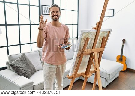 Young hispanic man with beard painting on canvas at home gesturing finger crossed smiling with hope and eyes closed. luck and superstitious concept.
