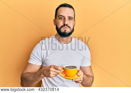Young man with beard drinking a cup coffee puffing cheeks with funny face. mouth inflated with air, catching air.