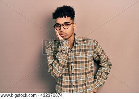Young african american man wearing casual clothes and glasses thinking looking tired and bored with depression problems with crossed arms.