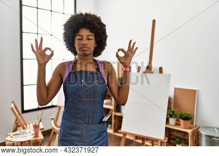 Young african american woman with afro hair at art studio relaxed and smiling with eyes closed doing meditation gesture with fingers. yoga concept.