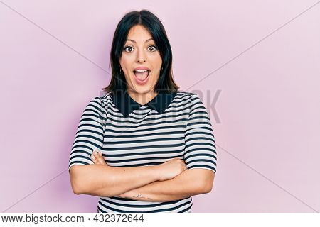 Young hispanic woman with arms crossed gesture celebrating crazy and amazed for success with open eyes screaming excited.