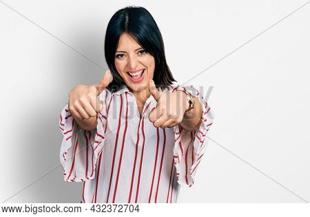 Young hispanic girl wearing casual clothes approving doing positive gesture with hand, thumbs up smiling and happy for success. winner gesture.