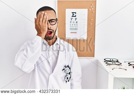 African american optician man standing by eyesight test yawning tired covering half face, eye and mouth with hand. face hurts in pain.