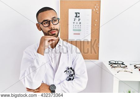 African american optician man standing by eyesight test with hand on chin thinking about question, pensive expression. smiling with thoughtful face. doubt concept.