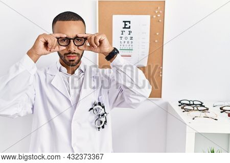 African american optician man standing by eyesight test trying to open eyes with fingers, sleepy and tired for morning fatigue