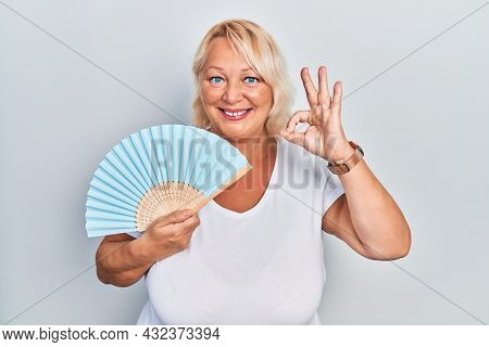 Middle age blonde woman waving hand fan cooling air in summer doing ok sign with fingers, smiling friendly gesturing excellent symbol