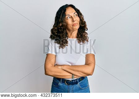 Middle age hispanic woman wearing casual white t shirt smiling looking to the side and staring away thinking.
