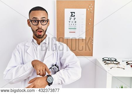 African american optician man standing by eyesight test in hurry pointing to watch time, impatience, upset and angry for deadline delay