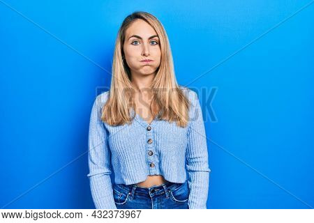 Young caucasian woman wearing casual clothes puffing cheeks with funny face. mouth inflated with air, crazy expression.