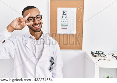 African american optician man standing by eyesight test doing peace symbol with fingers over face, smiling cheerful showing victory