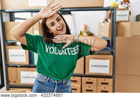 Young brunette woman wearing volunteer t shirt at donations stand smiling cheerful playing peek a boo with hands showing face. surprised and exited