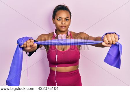Young african american girl training arm resistance with elastic arm bands skeptic and nervous, frowning upset because of problem. negative person.