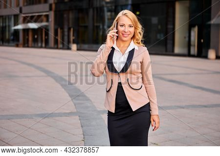 Attractive Business Woman Talking On Phone Near An Office Building.