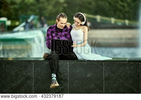 Young Couple On An Outdoor Date Uses Laptop Computer To Listen To Music Through Wireless Headphones.