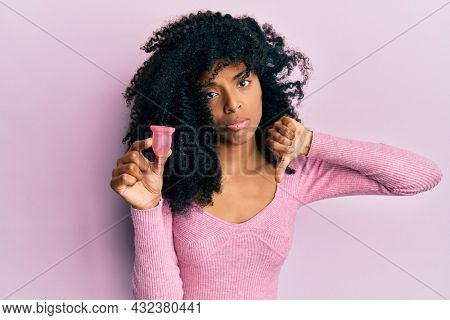 African american woman with afro hair holding menstrual cup with angry face, negative sign showing dislike with thumbs down, rejection concept