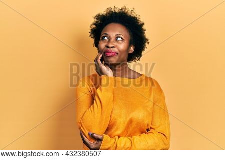 Young african american woman wearing casual clothes with hand on chin thinking about question, pensive expression. smiling and thoughtful face. doubt concept.