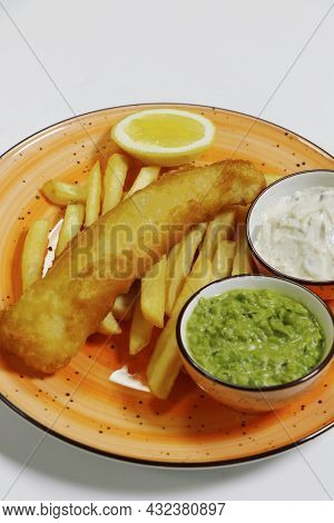 Fish And Chips With Tartar Sauce, Mushy Peas And Potato Fries